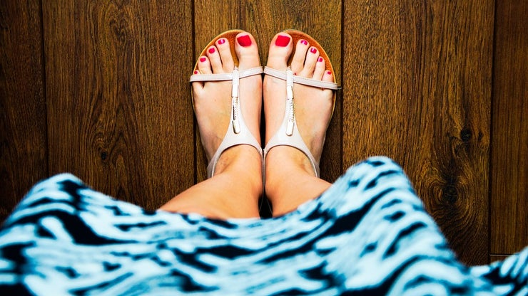 Feet wearing sandals with red painted toenails