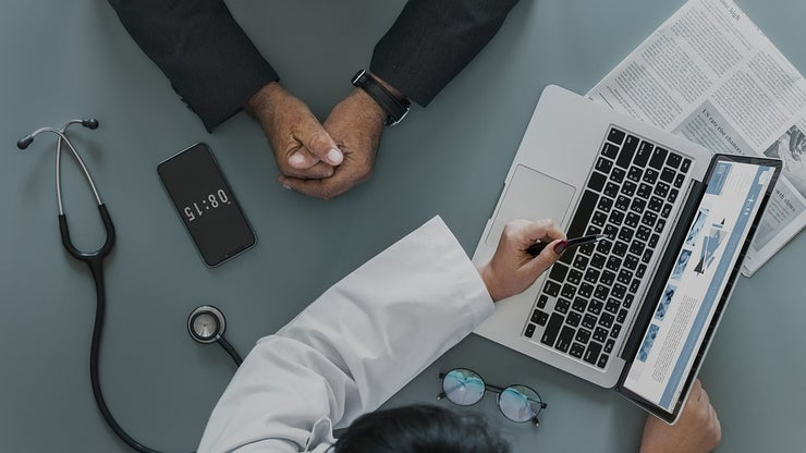 Doctor meeting with a patient in front of a laptop