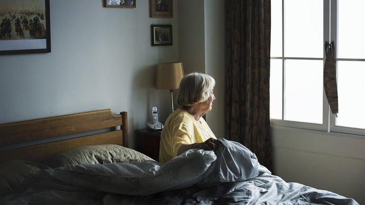 Older adult sitting in bed.